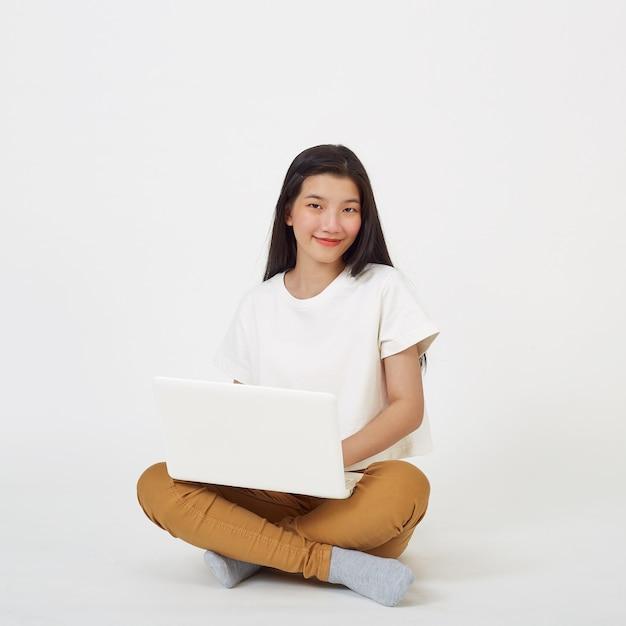 Glimlachende aziatische vrouw die op laptopcomputer werkt zittend op de vloer met gekruiste benen geïsoleerd over witte achtergrond, terug naar school concept