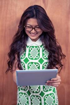 Glimlachende aziatische vrouw die tablet gebruiken tegen houten muur