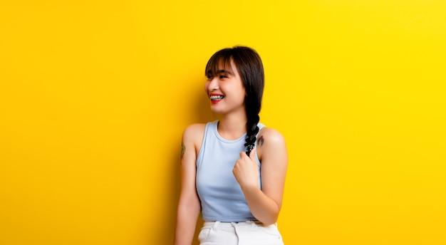 Glimlachende aziatische vrouw die tekenen van geluk vertoont, leeft gelukkig een goede gezondheid optimistische kijk op de wereld op een gele achtergrond