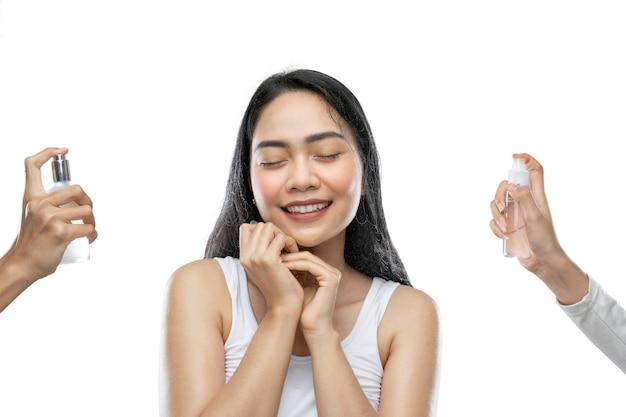 Glimlachende aziatische vrouw die witte onderjurk droeg, sloot haar ogen toen ze twee flessen serum spoot