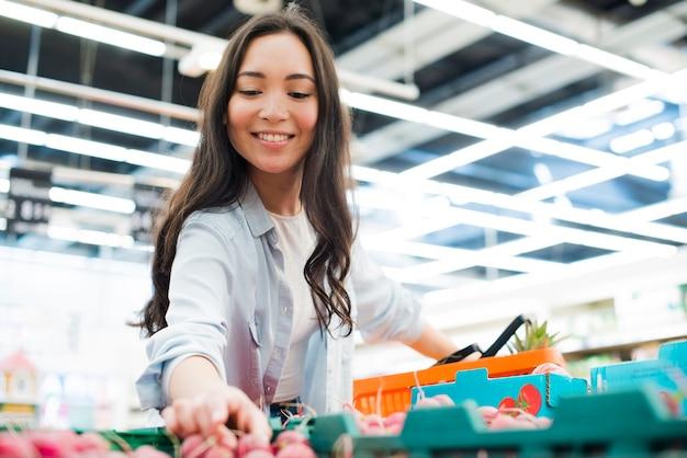 Glimlachende aziatische vrouw het plukken radijs in markt