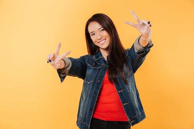 Glimlachende aziatische vrouw in denimjasje die vredesgebaren tonen