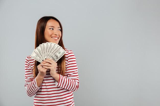 Glimlachende aziatische vrouw in het geld van de sweaterholding en weg het kijken over grijze achtergrond
