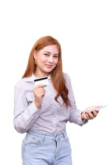 Glimlachende aziatische vrouw in toevallig overhemd die mobiele telefoon houden en creditcard voor online het winkelen tonen