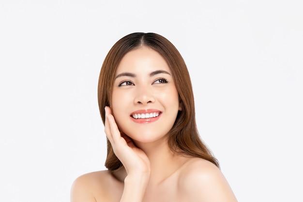 Glimlachende aziatische vrouw met eerlijke huidhand wat betreft haar gezicht