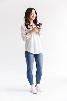 Glimlachende aziatische vrouw met lang donker haar die en zwarte mobiele telefoon houden gebruiken