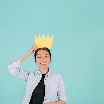 Glimlachende aziatische vrouw met papieren kroon