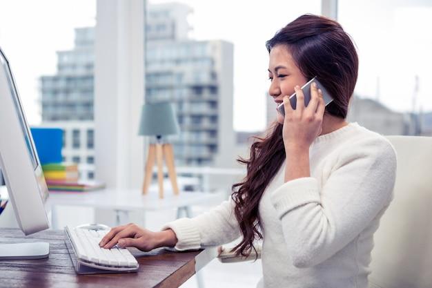 Glimlachende aziatische vrouw op een telefoongesprek die computer in bureau met behulp van