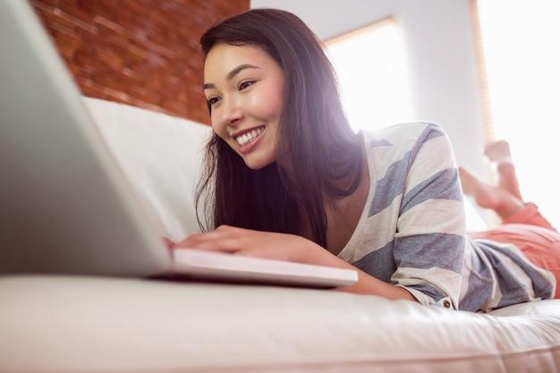 Glimlachende aziatische vrouw op laag die laptop met behulp van