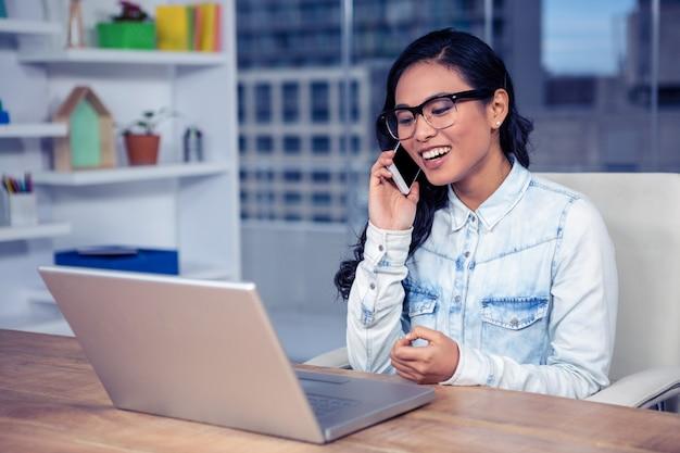 Glimlachende aziatische vrouw op telefoongesprek in bureau