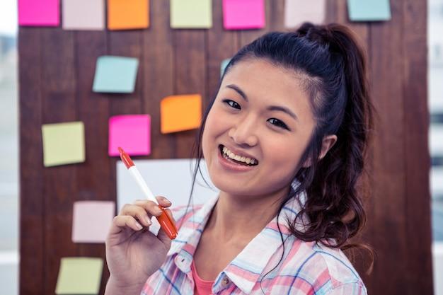 Glimlachende aziatische vrouw tegen houten muur met nota's over het