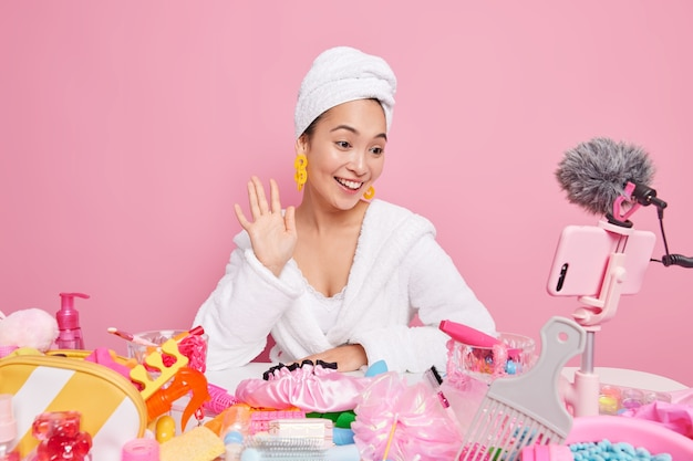 Glimlachende aziatische vrouwelijke beautyblogger filmt make-uphandleiding en zwaait hallo in smartphonecamera