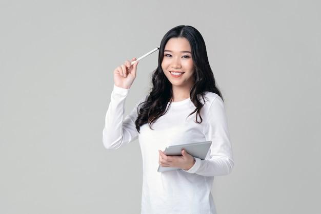 Glimlachende aziatische vrouwenholding tablet en naaldpen in het denken van gebaar
