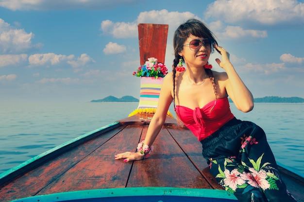 Glimlachende aziatische vrouwenzitting op traditionele thaise houten lange staartboot tijdens haar vakantie in thailand