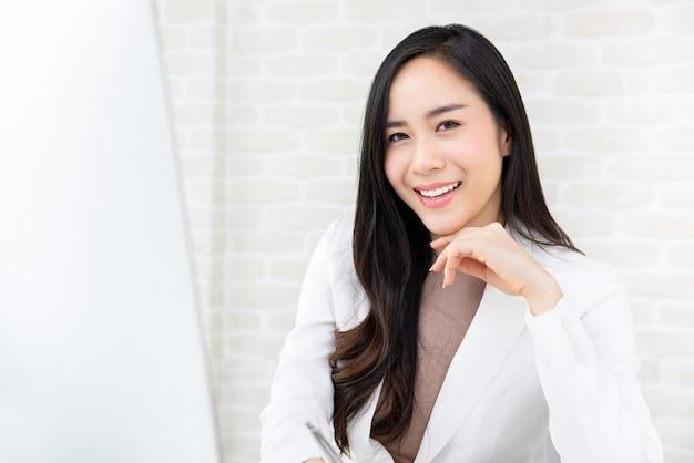 Glimlachende aziatische werkende vrouw in wit kostuum