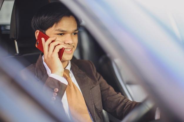 Glimlachende aziatische zakenman bestuurt een auto terwijl hij een gesprek voert op een smartphone