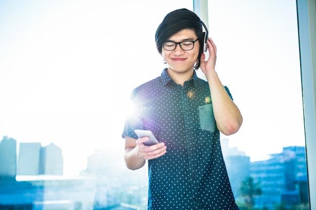 Glimlachende aziatische zakenman die aan muziek in bureau luisteren