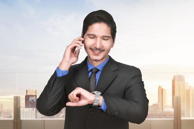 Glimlachende aziatische zakenman die op de mobiele telefoon spreekt terwijl het controleren van tijd