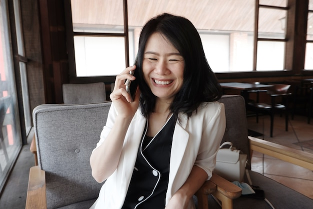 Glimlachende aziatische zakenvrouw belt met smartphone online die op sociale media werkt