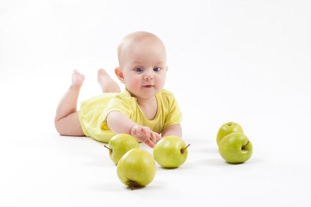 Glimlachende baby die op de grond ligt om appelen op te nemen