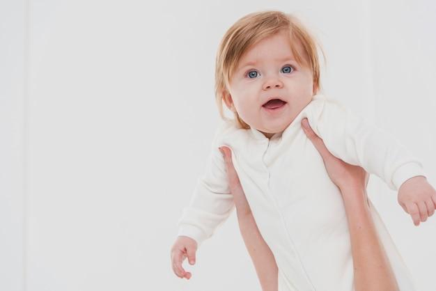 Glimlachende baby gehouden voor pose