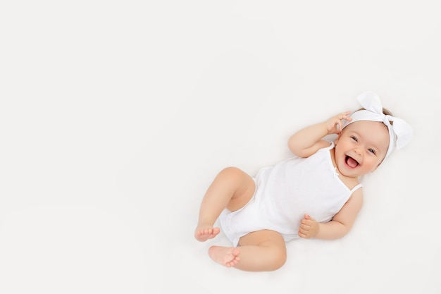 Glimlachende baby op een wit bed thuis