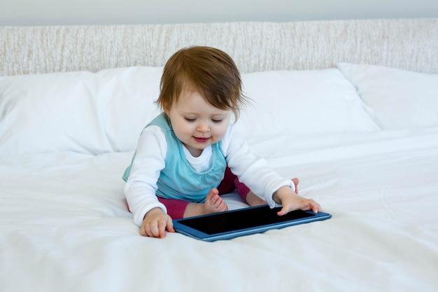 Glimlachende baby spelen met een tablet op een bed