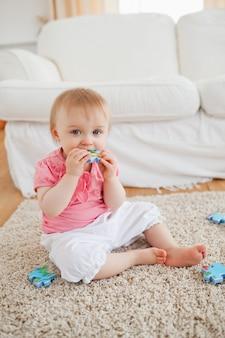 Glimlachende baby spelen met puzzelstukjes zittend op een tapijt