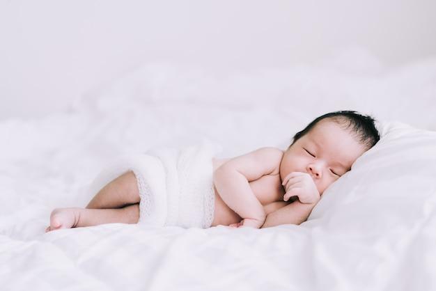 Glimlachende babyjongen die op een wit bed ligt