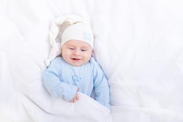 Glimlachende babyjongen op het bed onder de deken in een pet