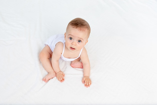 Glimlachende babymeisje, zittend in een wieg in een kinderkamer in witte kleren, bovenaanzicht