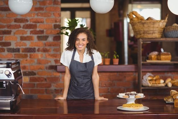 Glimlachende barista die op teller leunt