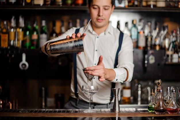 Glimlachende barman schudt een mooie cocktail