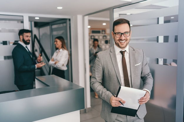 Glimlachende bebaarde blanke zakenman in formele kleding en met bril staande op hal. wees niet bang voor wat er mis kan gaan en bedenk wat er goed kan gaan.