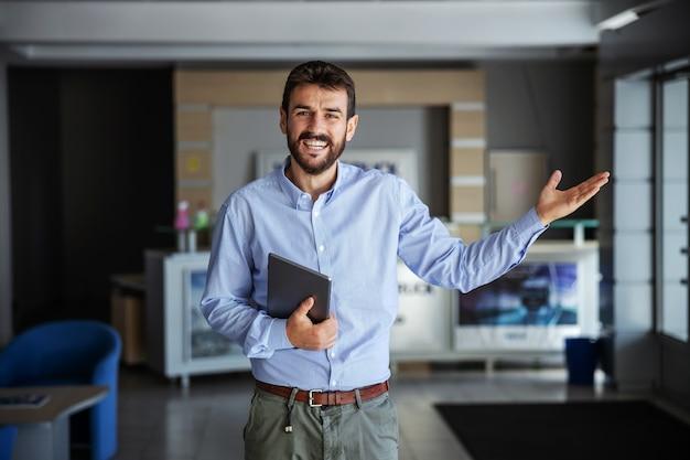Glimlachende bebaarde ceo die in de lobby van de verzendfirma staat, tablet vasthoudt en gebaren bezorgt is op tijd en alles gaat goed.