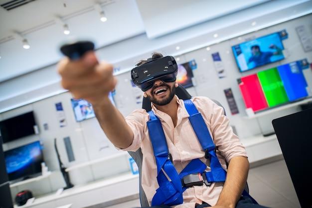 Glimlachende bebaarde man die de draadloze joystick in de hand houdt tijdens het testen van een vr-bril en zittend in een stoel met veiligheidsgordels in een technische winkel