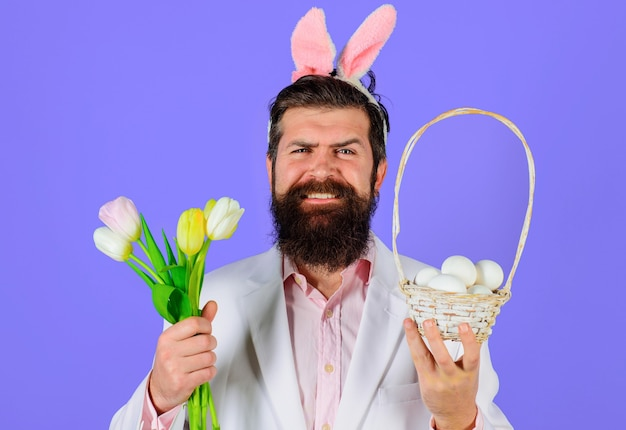 Glimlachende bebaarde man in konijnenoren met mand met paaseieren en bloemboeket op paarse achtergrond