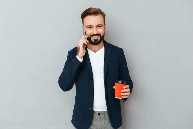 Glimlachende bebaarde man in zakelijke kleding praten door smartphone