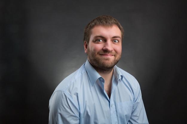 Glimlachende bebaarde man met een blauw shirt over grijs