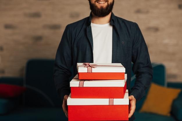 Glimlachende bebaarde man met geschenkdozen in handen. positieve menselijke emotie, gevoel en houding voor vakanties.
