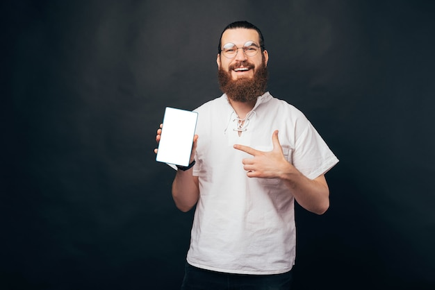 Glimlachende bebaarde man wijst naar zijn tablet.