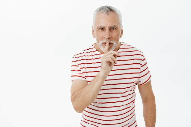 Glimlachende bebaarde senior man vragen geheim houden, zwijgen, verrassing voorbereiden
