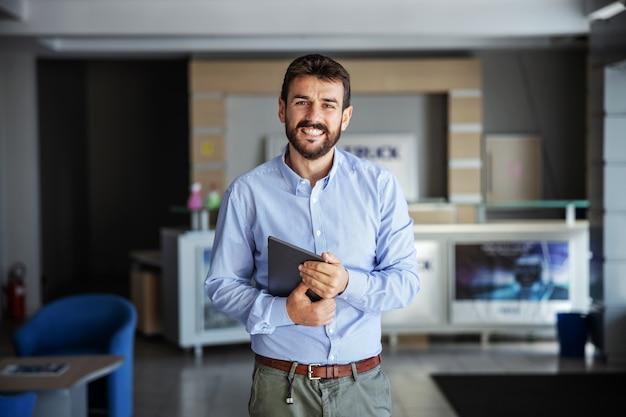 Glimlachende bebaarde zakenman die zich in lobby van verzendbedrijf bevindt en tablet houdt. levering is altijd op tijd.