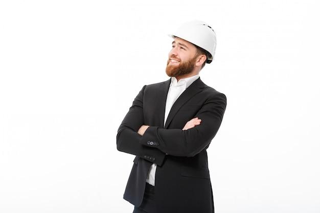 Glimlachende bebaarde zakenman in beschermende helm bedrijf gekruiste armen