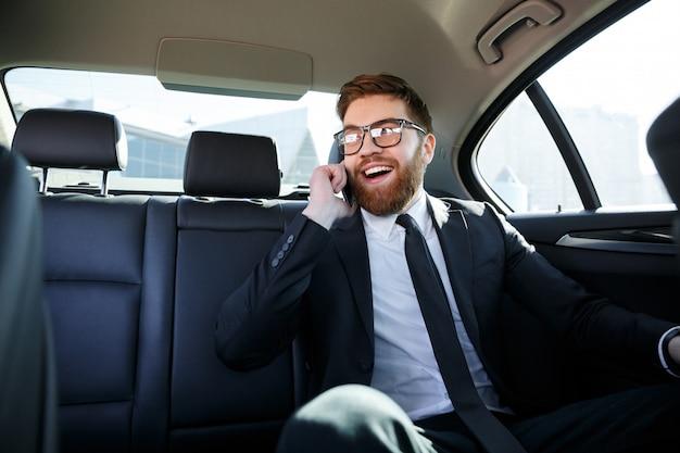 Glimlachende bebaarde zakenman in brillen praten op mobiele telefoon