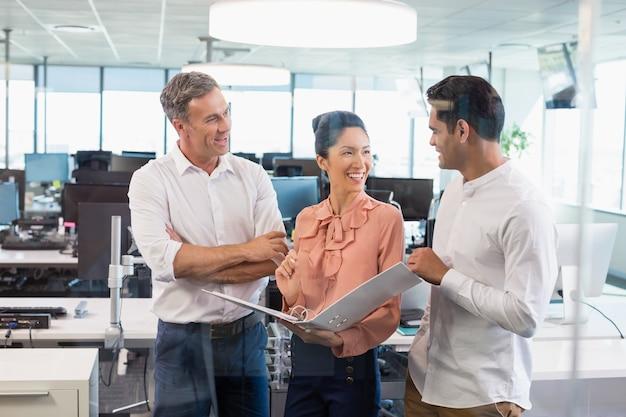 Glimlachende bedrijfscollega's die over klembord bij bureau bespreken