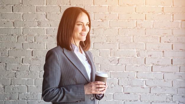 Glimlachende bedrijfsleider in witte blouse en grijs klassiek kostuum drinkt koffie uit een papieren beker die tegen de muur staat voor het werk close-up, zonlicht