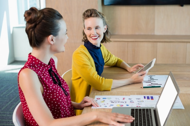 Glimlachende bedrijfsleiders die met elkaar in vergaderruimte in wisselwerking staan