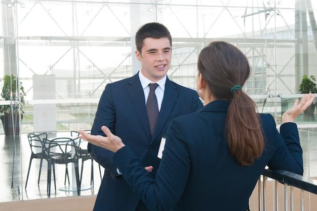 Glimlachende bedrijfsmens die met vrouwelijke collega in openlucht spreekt