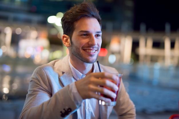 Glimlachende bedrijfsmens die na het werk een cocktail drinkt